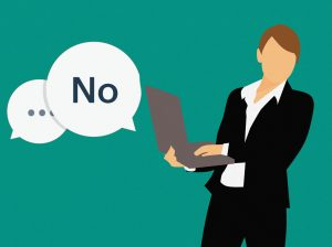 "A person at work with a speech bubble saying ""no"""